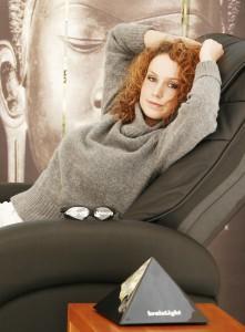 Anwenderin auf einem brainLight-Komplettsystem bestehend aus audio-visueller Entspannung und Shiatsu-Massagesessel.
